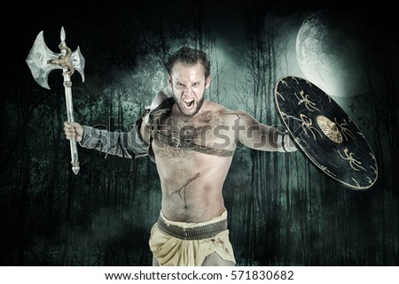 Ancient warrior or Gladiator posing in a dark forest with an axe