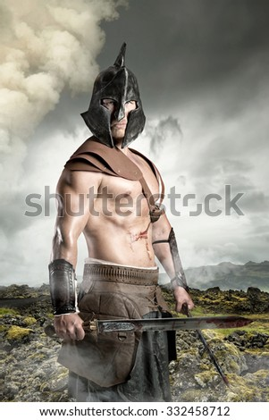 Ancient warrior posing outdoors with swords ready for battle - stock photo