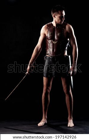 Ancient Warrior with sword on black background - stock photo