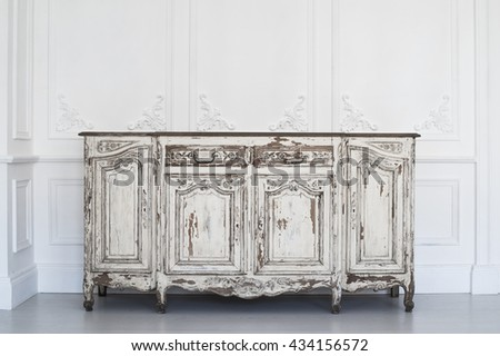 Ancient white commode bureau with paint peeled off on luxury wall design bas-relief stucco mouldings roccoco elements  - stock photo