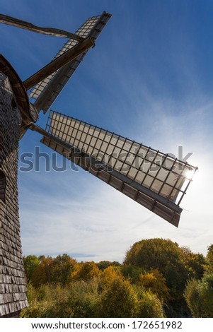 ancient windmill with covered vane in sunlight - stock photo
