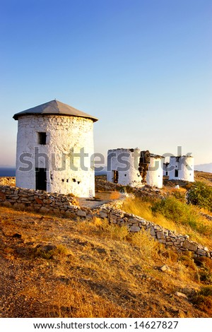 ancient windmills on sunset - stock photo