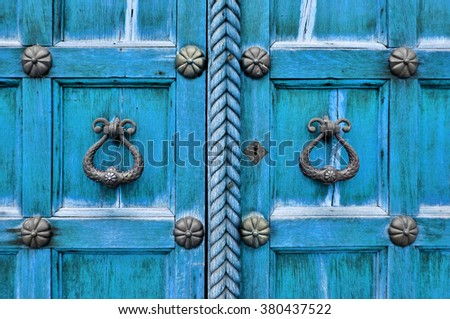 Ancient wooden bright turquoise door with aged metal door handles and rivets. Architectural detailed background - stock photo