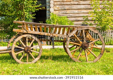 Ancient wooden cart standing on the lawn in the courtyard