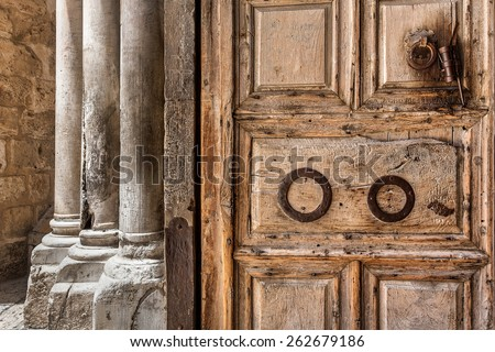 Ancient wooden door and marble pillars at the entrance to Church of the Holy Sepulchre in Jerusalem, Israel. - stock photo