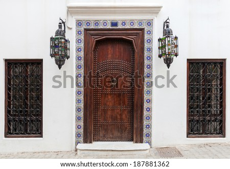 Ancient wooden door and windows on white wall. Tangier, Morocco - stock photo