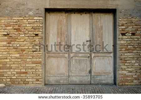 Ancient wooden door in Montelupone (IT) - stock photo