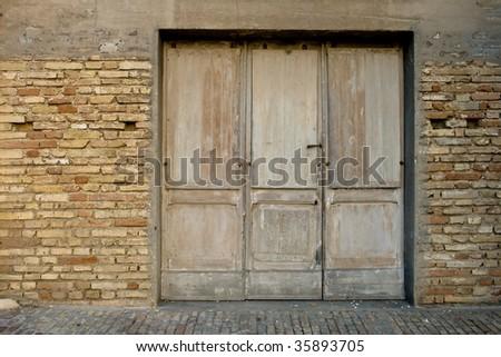 Ancient wooden door in Montelupone (IT) - stock photo