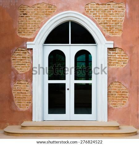 Ancient wooden door in stone castle wall. - stock photo