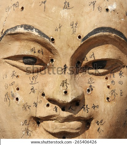 Ancient wooden face showing acupuncture points  - stock photo