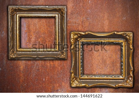 ancient wooden frames on rusty metal wall background
