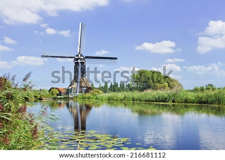 Ancient wooden windmill mirrored in a canal on a summer day with a blue sky and dramatic clouds.