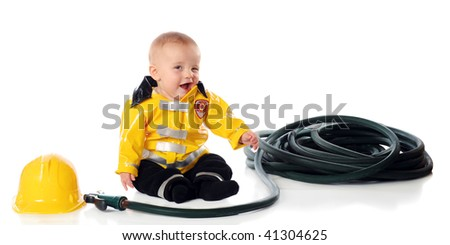 And adorable baby boy winking while wearing a fireman's suit, wit his hat and hose nearby.  Isolated on white. - stock photo