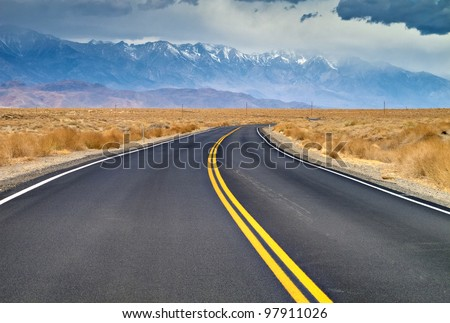 And empty road headed into Lone Pine, California.  The Eastern Sierra Mountains can be seen in the background with snow caps - stock photo