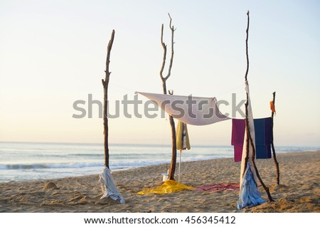 And improvised DYI shade at a wild beach at sunrise. - stock photo