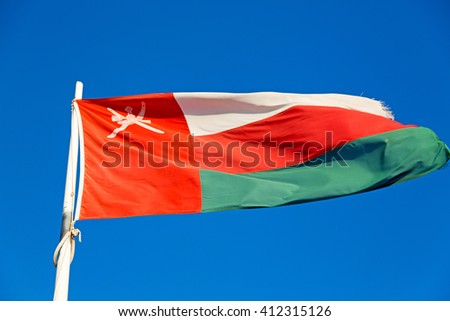 and the cloudy sky in oman waving flag  - stock photo