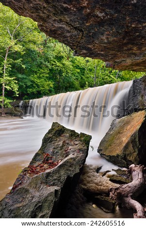 Anderson Falls, a wide, beautiful waterfall near Columbus, Indiana, has a rock grotto on one side with fallen boulders. - stock photo