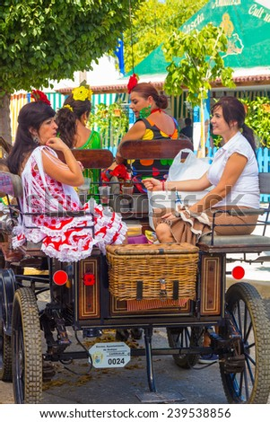 ANDUJAR,SPAIN - September, 6: Women typical Sevillian flemanca suits, walking in the car in the Horse Fair on September, 6, 2014 in Andujar, Spain - stock photo