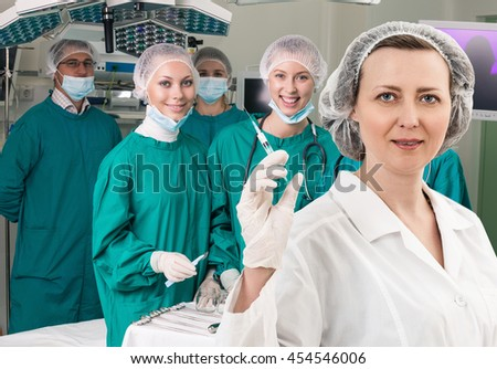 Anesthetist with syringe and surgery teem
