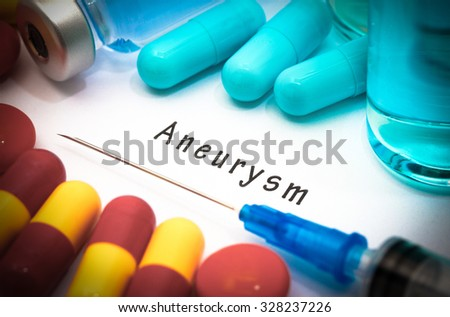 Aneurysm - diagnosis written on a white piece of paper. Syringe and vaccine with drugs. - stock photo