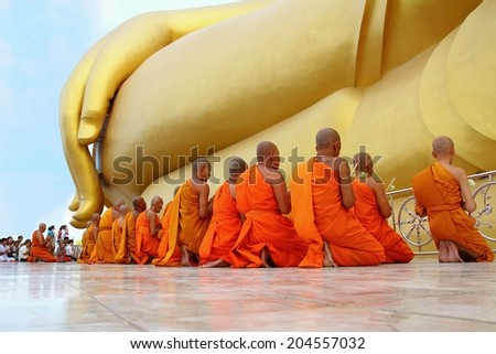 Ang Thong, Thailand-July 11,2014: Buddhists and monks walk with lighted candles clockwise round the temple, Asaha Puja Day and the beginning of Buddhist Lent, at Wat Muang- Ang Thong, Thailand. - stock photo