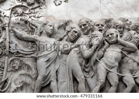 Angel and sinners in the Doomsday. A relief on an external wall of the Cathedral Duomo in the city of Orvieto, Umbrija, Italy