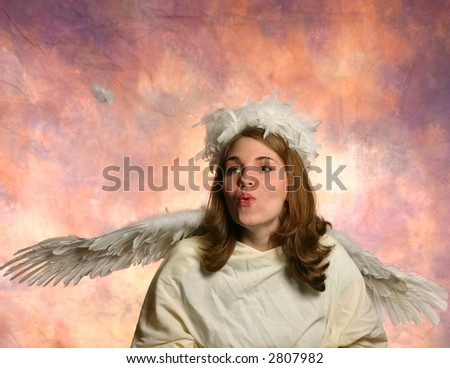 Angel blowing a feather - stock photo