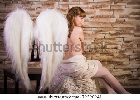 angel girl on brick wall background - stock photo