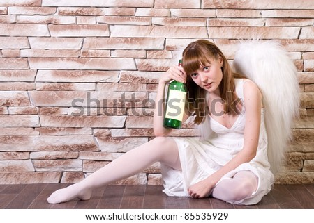Angel girl on brick wall with a bottle. Sitting pose. - stock photo