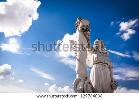 Angel in light: old angel sculpture against bright blue sky and white clouds. Copy space. - stock photo