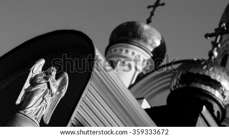 Angel on the background of the church,black and white photo,horizontal photo - stock photo