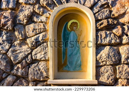 Angel picture in aedicula on house stone wall in Medjugorje in Bosnia ed Erzegovina - stock photo