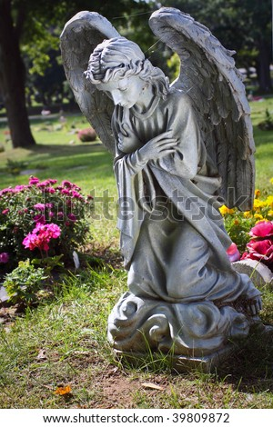 Angel praying in flowers - stock photo