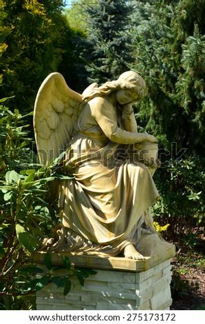 angel sculpture in the garden - stock photo