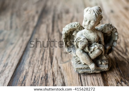 angel sculpture on wooden background - stock photo
