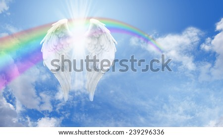 Angel Wings - Floating Angel wings with an arcing rainbow and bright sunburst behind on a blue sky background with plenty of copy space on the right hand side - stock photo
