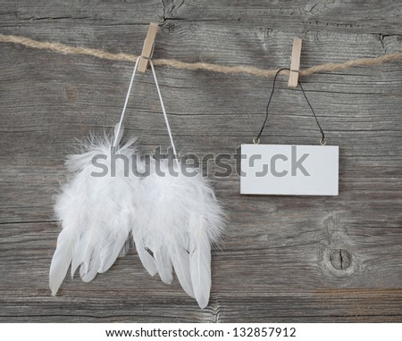 Angel wings with a blank note on grey wooden background - stock photo