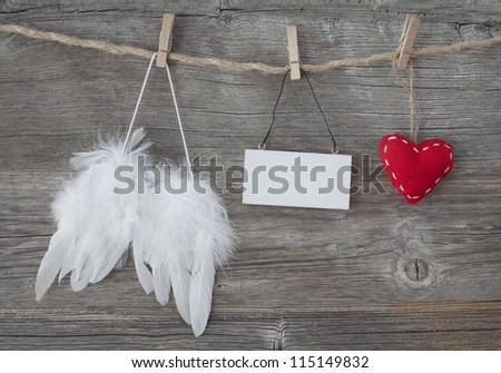 Angel wings with heart and blank note on grey wooden background - stock photo