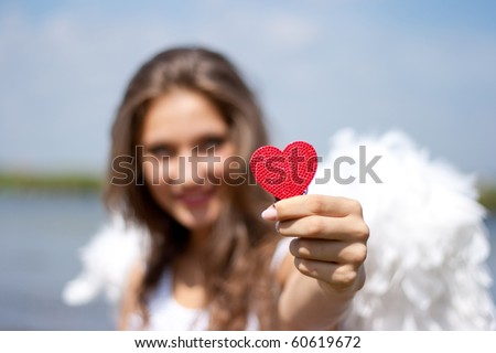 Angel with red heart outdoors