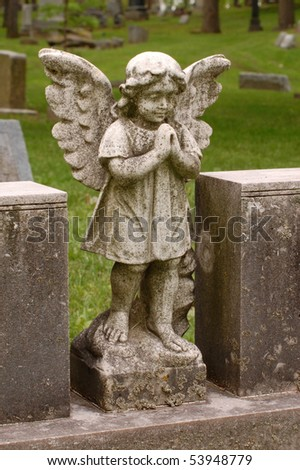 Angel with wings between two headstones in cemetery - stock photo