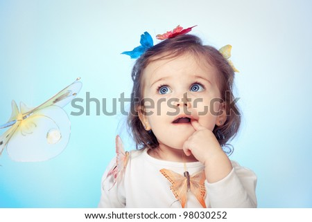 Angelic baby girl looking puzzled, over blue