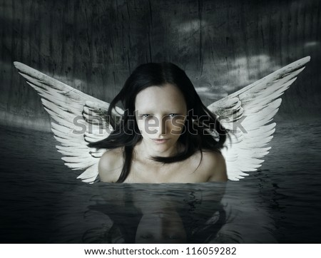 Angelic being that comes out of the water in a setting dark background - stock photo