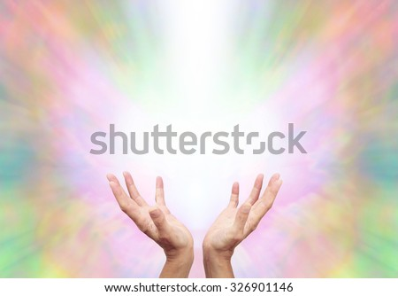 Angelic Energy Healer - Female energy worker with hands outstretched and open upwards sensing healing energy on ethereal rainbow colored  energy formation background - stock photo