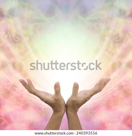 Angelic Healing Energy -  Female hands outstretched sensing a beautiful pastel colored Angelic energy field with a ball of white light at the center and plenty of copy space around - stock photo