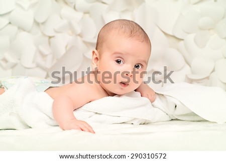 Angelic little baby lying on white blanket. Healthcare. Happy childhood. Background of tender white flowers.  - stock photo