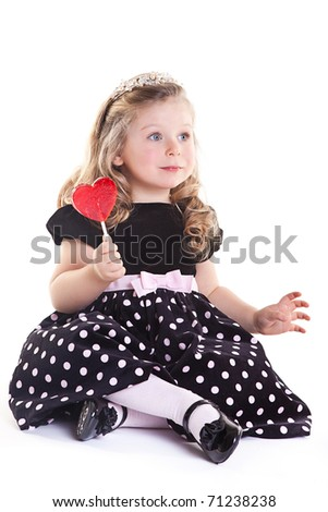 Angelic little girl sitting on white background and holding red heart lollypop