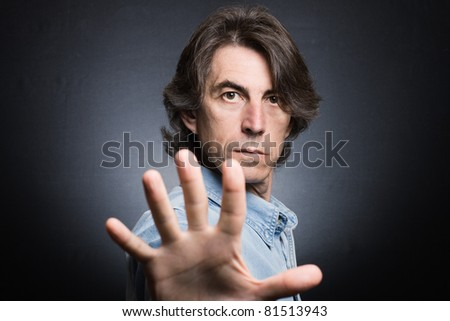 Anger man signaling a stop sign on a black background - stock photo