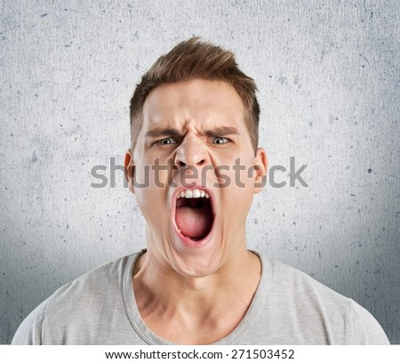 Anger. Portrait of young angry man - stock photo