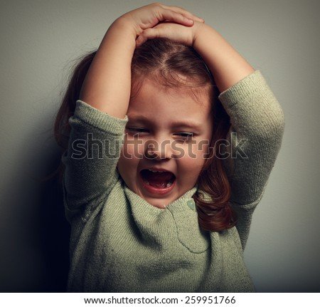 Anger shouting kid holding head with open mouth. Closeup vintage portrait - stock photo