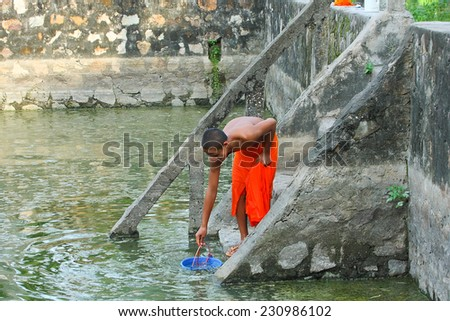 ANGIANG,VIETNAM - FEB 07,2009: A young monk is getting water from a cistern at An Giang province, Southern of Vietnam. - stock photo